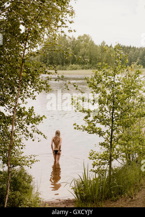 Rear view of woman standing and looking out from lake, Orivesi, Finland - Stock Photo