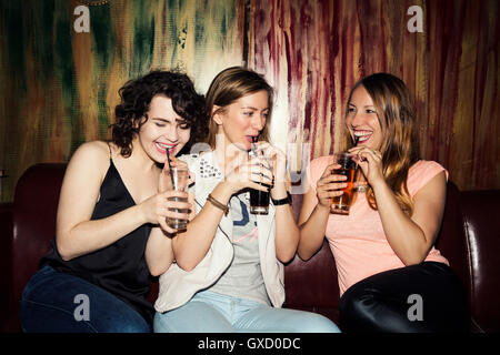 Three adult female friends drinking in bar - Stock Photo