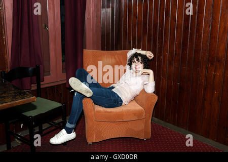 Portrait of young woman reclining on armchair on night out in bar - Stock Photo