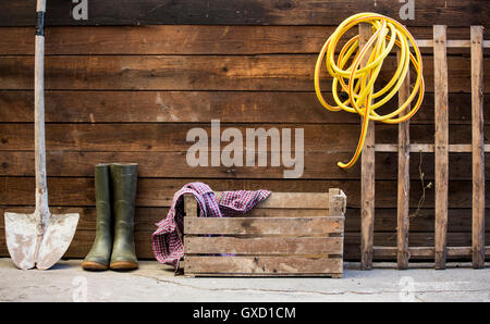 Row of spade, rubber boots and hosepipe by shed - Stock Photo