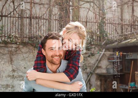 Man giving woman piggyback smiling - Stock Photo