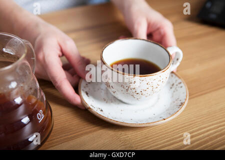 White cup of coffee in hand. Barista holding coffee - Stock Photo