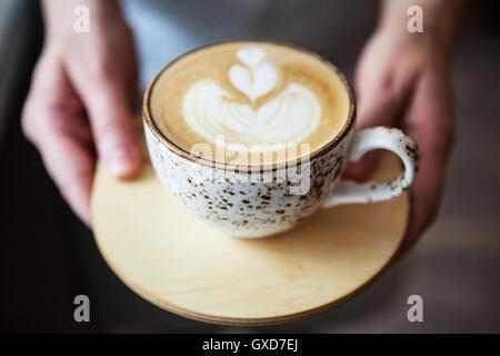 Coffee cup. Latte art in cafe. Barista offering coffee - Stock Photo