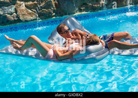 Mature couple in swimming pool, relaxing on inflatables - Stock Photo