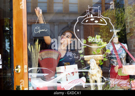 Female worker in bakery, turning sign to open - Stock Photo