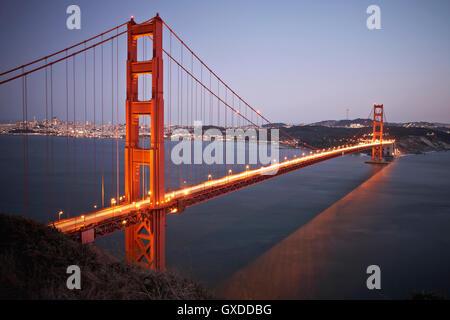 View of traffic light trails crossing Golden Gate Bridge at dusk, San Francisco, California,  USA - Stock Photo