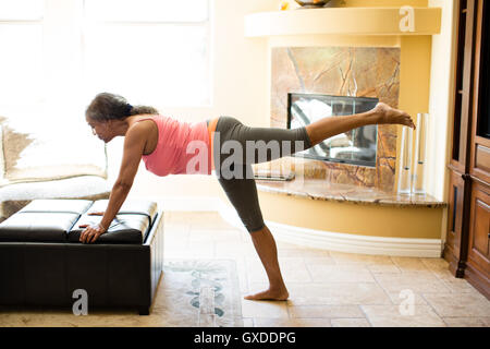 Side view of woman leaning against pouffe doing stretching exercise - Stock Photo