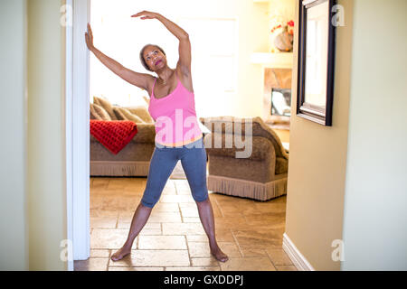 Woman with arms raised doing stretching exercise - Stock Photo