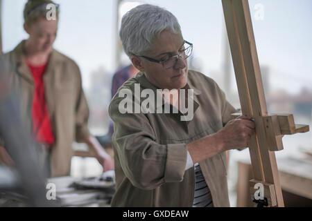 Female carpenter putting up easel in furniture making workshop - Stock Photo