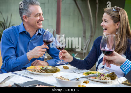 Mature friends making a red wine toast at garden party table - Stock Photo