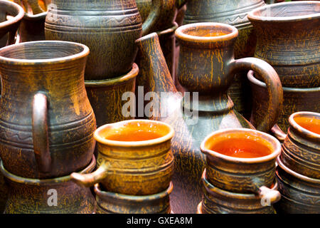 Handmade traditional russian ceramics (crockery, things, ware, jugs, pots) on the shopboard at the flea market in - Stock Photo