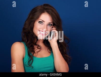 Emotional excited young woman talking on mobile phone on blue background - Stock Photo