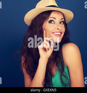 Happy smiling fun makeup woman in summer hat thinking and looking on blue background. Closeup bright portrait - Stock Photo