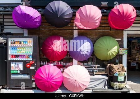 Japan, Izushi. Otemae-dori, main tourist shopping street. Souvenir one colour in various colours, umbrellas displayed - Stock Photo