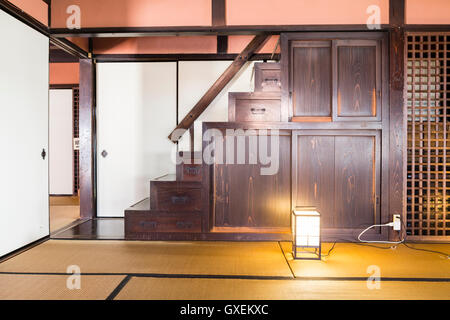 Japan, Izushi. Izushi Shiryokan museum, interior. Large tatami mat room with staircase with built in storage cupboard - Stock Photo