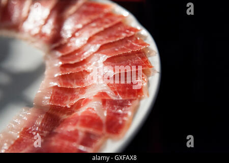 Half decorated arrangement of iberian cured ham on plate isolated over black background - Stock Photo