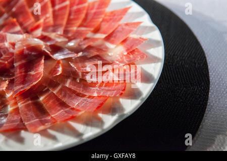 Circular decorative arrangement of iberian cured ham on plate. Selective focus point - Stock Photo