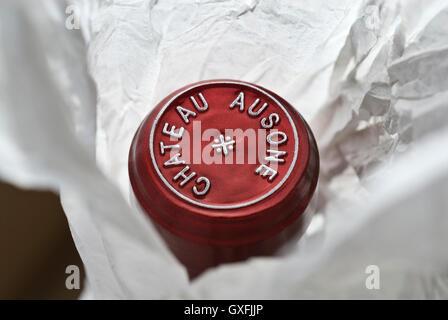 Close view on unwrapped bottle with encapsulation foil seal of fine luxury Chateau Ausone Saint-Émilion red wine - Stock Photo