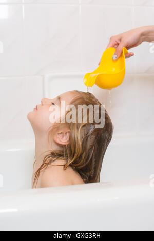 Caucasian mother rinsing hair of daughter in bathtub - Stock Photo