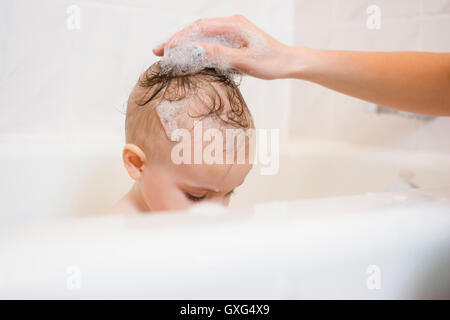 Caucasian mother washing hair of baby daughter in bathtub - Stock Photo