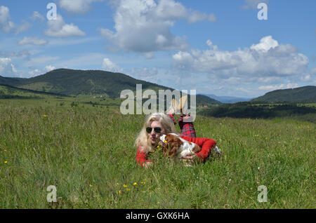 Woman dressed in red lying with her dog (Cavalier King Charles Spaniel) on a mountain meadow and divine landscape - Stock Photo