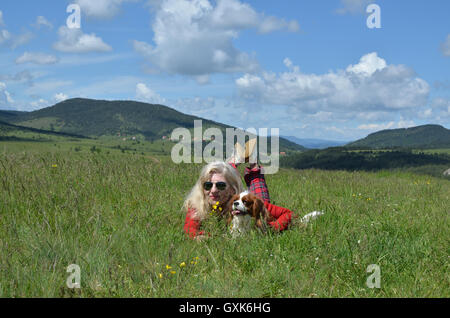 Woman dressed in red lying with her dog (Cavalier King Charles Spaniel) on a mountain meadow and lovely landscape - Stock Photo