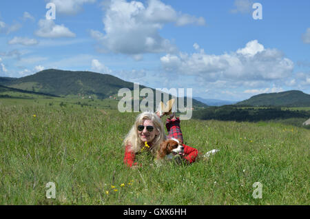Woman dressed in red lying with her dog (Cavalier King Charles Spaniel) on a mountain meadow and spring landscape - Stock Photo