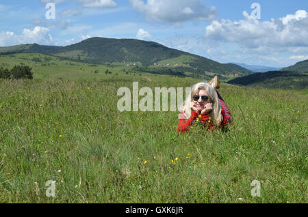 Woman dressed in red lying and relaxing on a mountain meadow, and lovely landscape in background - Stock Photo