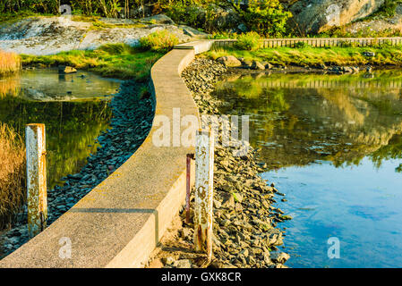 Narrow, bending concrete pier leading out to a wooden walkway on an island across the water. The archipelago surrounding - Stock Photo