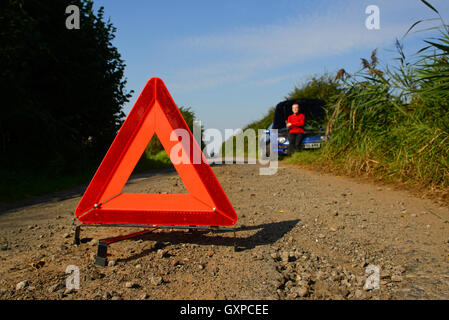 hazard warning triangle on country road warning of man with broken down vehicle ahead york yorkshire uk - Stock Photo