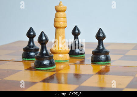 King surrounded by pawns on a white background. games and themes - Stock Photo