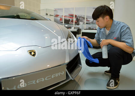 Chinese man cleans a Lamborghini at a showroom in AUDI China in Beijing, China. 05-Sep-2016 - Stock Photo
