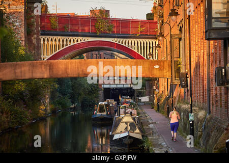 Manchester canal lock 92   locks  Castlefield canal boats jogger running towpath urban city scene golden sunshine - Stock Photo