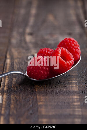 Raspberries on old spoon on grunge wooden board. Natural healthy food. Still life photography - Stock Photo