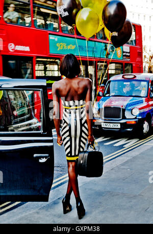 London Fashion Week February 2013, Attractive Fashion Model poses with balloons amidst London traffic, London WC2, - Stock Photo