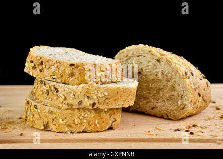 Sliced granary baguette on chopping board, against a black background - Stock Photo