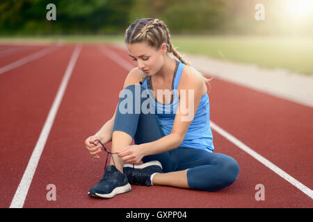Sporty young woman sitting on a race track at a sports stadium smiling as she ties her laces on her running shoes - Stock Photo