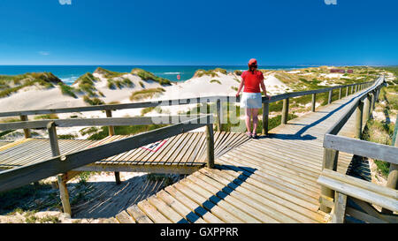 Portugal: Woman enjoying beach and sea view at a wooden walking path in Praia de Comporta - Stock Photo