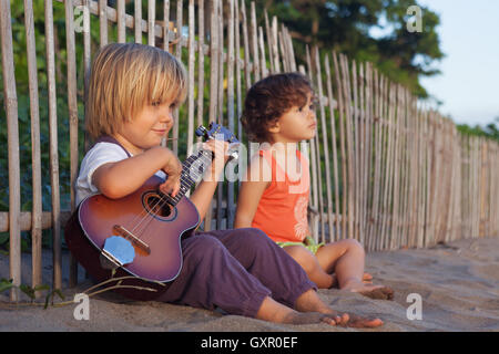 Little happy children have fun, play music on Hawaiian guitar ukulele for small baby girl, enjoying sunset ocean - Stock Photo