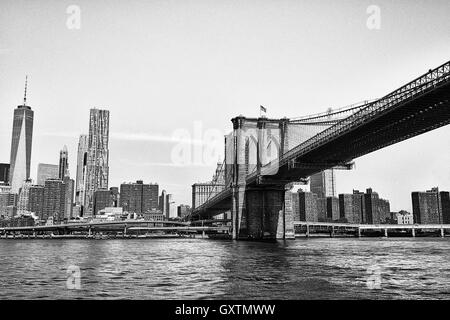 The Brooklyn Bridge, crossing over the East River into lower Manhattan - Stock Photo