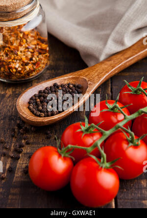 Fresh tomatoes with basil and spoon with pepper on grunge wooden board. Jar with spices - Stock Photo