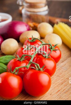 Fresh organic tomatoes with vegetables on wooden board. Potatoes,onion,sauce.spices,basil - Stock Photo