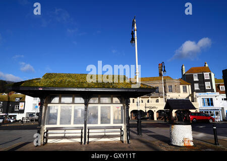 Old fashioned bus shelter and wishing well on sea front on Old Town, Hastings, East Sussex, England - Stock Photo