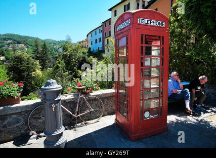 Two men on a bench near the 'wee library' British phone box at Barga in Tuscany, Italy. The town has a very close - Stock Photo