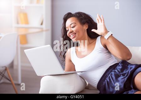 Joyful young woman talking through the Internet - Stock Photo