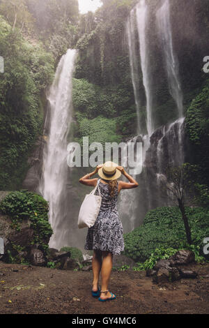 Rear view shot of female tourist admiring beautiful waterfall in tropical rain forest. Young woman looking at waterfall. - Stock Photo