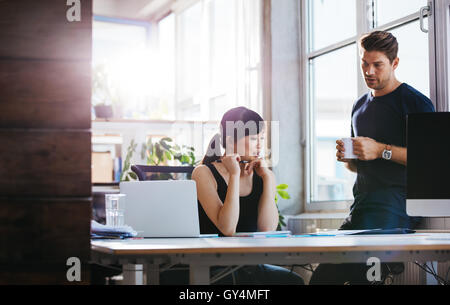 Two young executive discussing new business ideas in office. Colleagues working together on paperwork. Woman sitting - Stock Photo