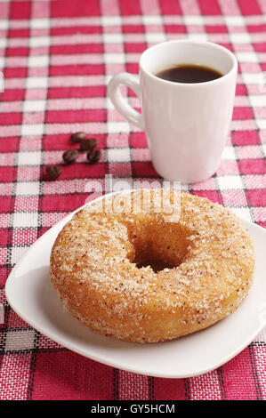 Breakfast with sweet donut and cup of black coffee on red tablecloth - Stock Photo