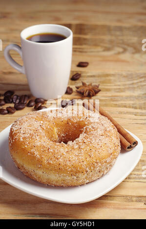 Tasty donut and black coffee on old wooden table - Stock Photo