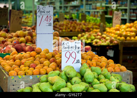 Fresh BC fruit for sale at a local produce market on Hastings Street in Burnaby.  Piles of bartlett pears and apricots. - Stock Photo